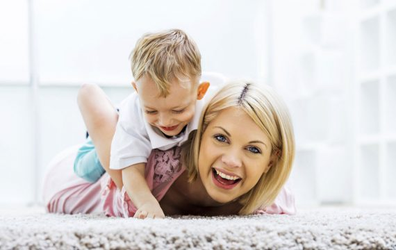 Happy Mum plays with son on fresh clean carpet